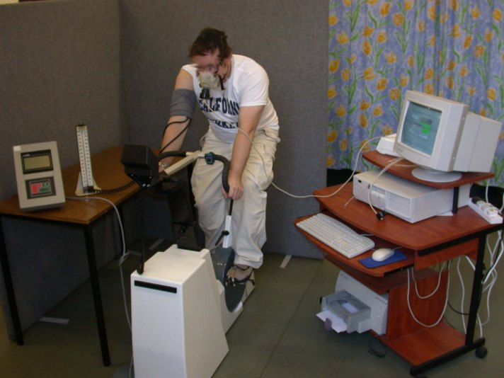A subject seated on a cycle ergometer. A heart rate monitor is worn across the chest under the clothing to measure pulse at rest and during exercise. The facemask is connected to a computer which analyses the expired for percentage oxygen, carbon dioxide and total volume. A blood pressure cuff is worn on the right arm to measure changing blood pressure during exercise. (Photo credit Dr. Nicole Burns)